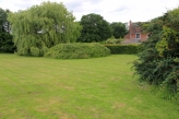 Photo 18: View to Golden Cross House across the pond (overgrown with brambles)